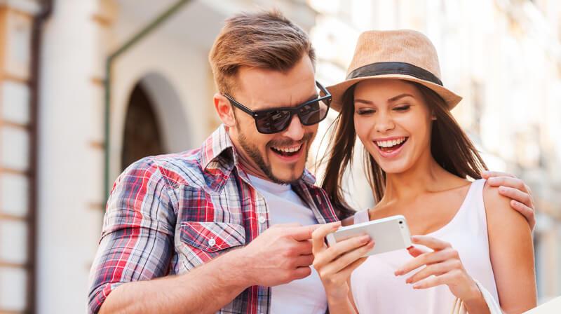 Junges Paar mit Sonnenbrille und Smartphone